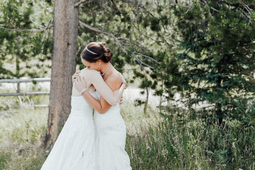 Two beautiful brides embrace during their first look