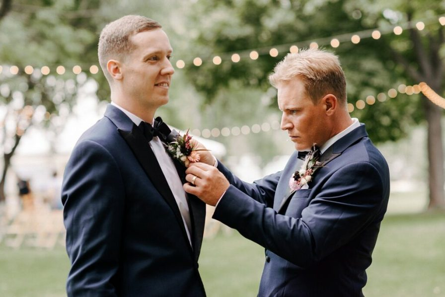 groomsman pinning on groom's boutonniere