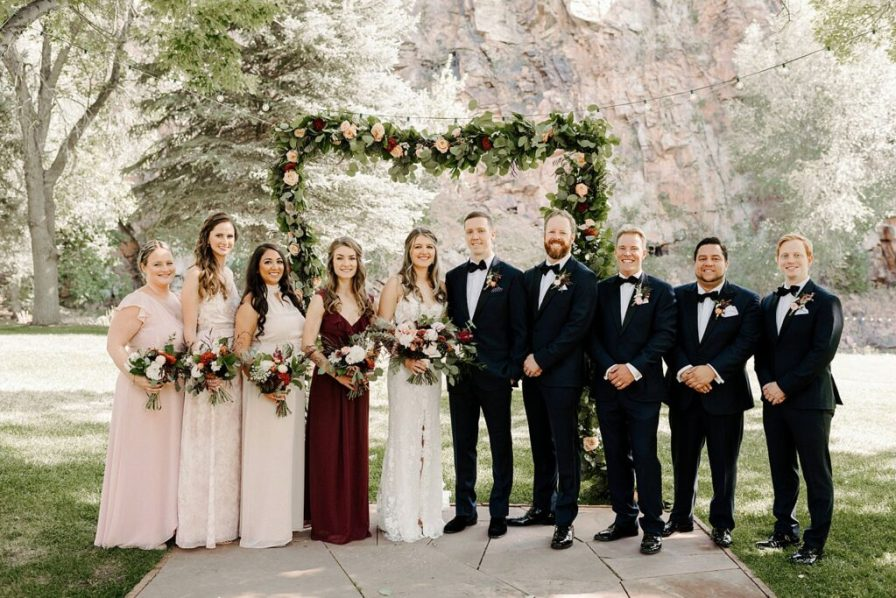 wedding party photos under the flower arch