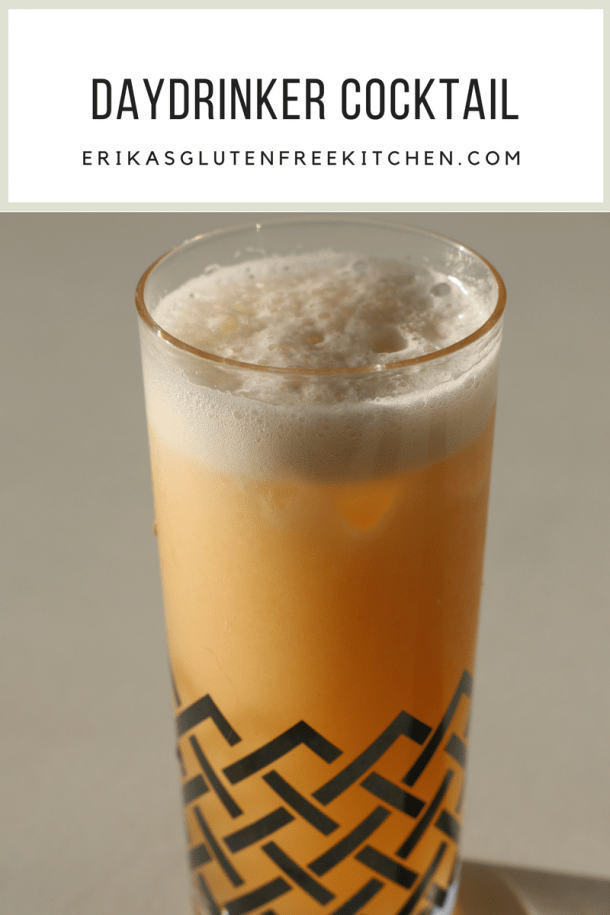 Tall orange-peach colored cocktail in a platinum decorated glass.