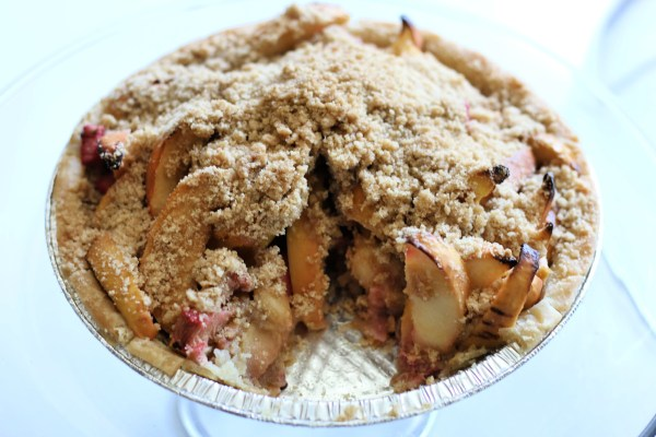 An image of an apple rhubarb pie with a slice cut out of it.