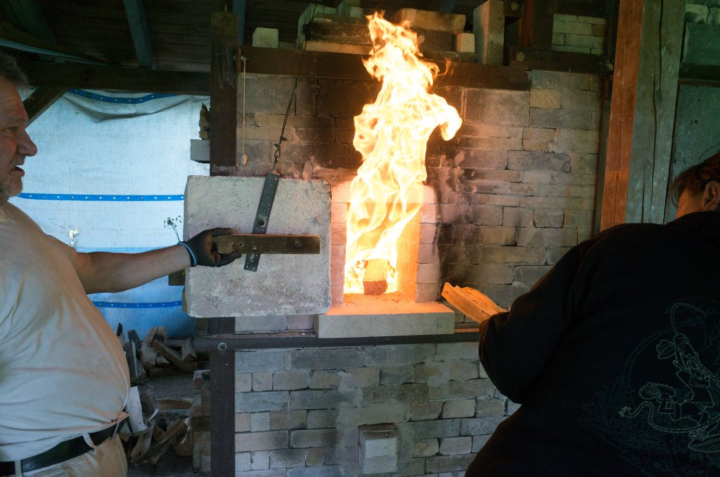Filling the kiln with wood: each few minutes, a few sticks branches entire tree trunks.