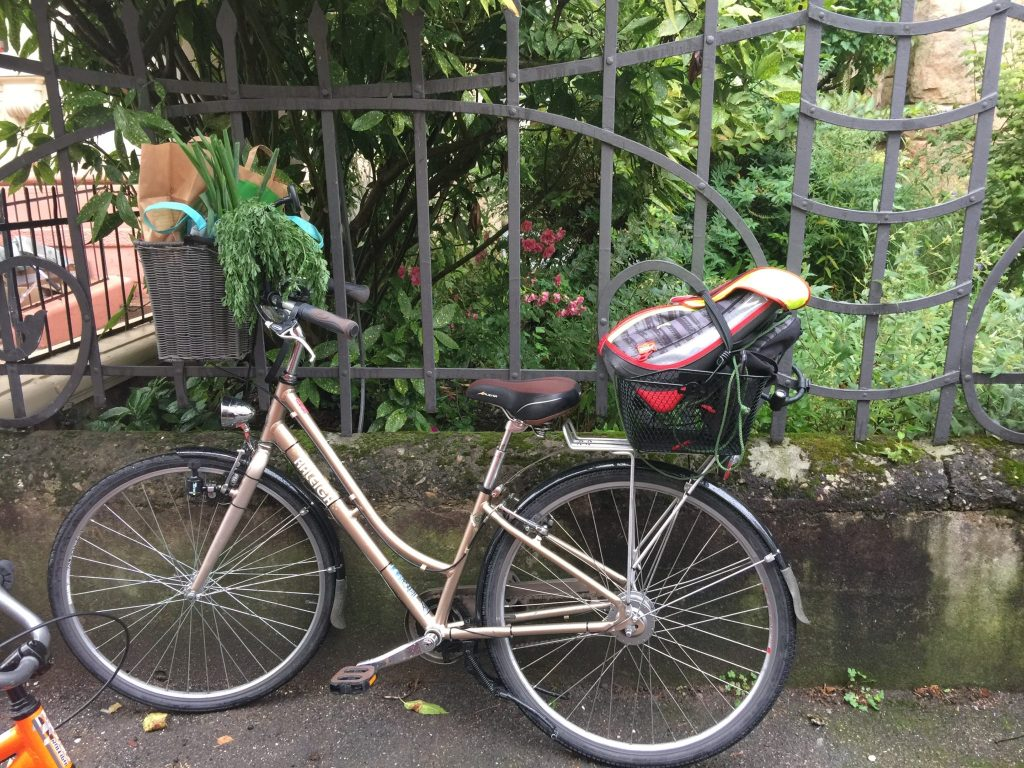 Cramming the shopping into my bike baskets, along with my son's school bag.
