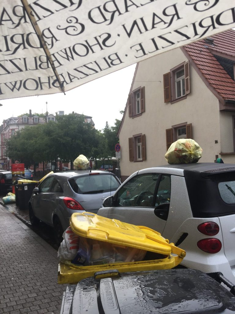When there's no room for your recycling on the narrow German streets, plop the bag on top of a car.