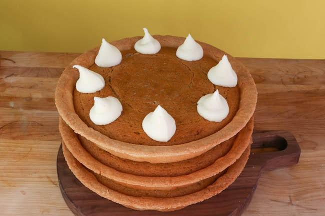Dollops of cream cheese frosting on a layered pumpkin cake pie. | Erin Gardner