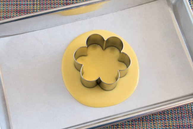 Flower-shaped cookie cutter set into melted yellow coating chocolate | Erin Gardner | Erin Bakes