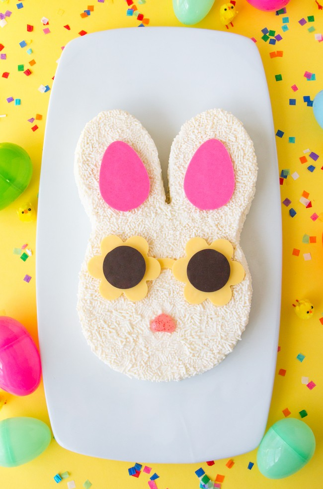 Bunny cake covered in white sprinkles with pink chocolate ears and yellow chocolate sunglasses | Erin Gardner | Erin Bakes