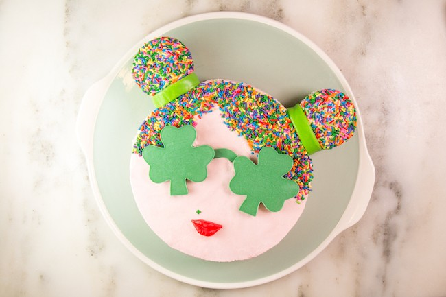 Round cake finished with buttercream, sprinkle hair, and shamrock-shaped green chocolate sunglasses | Erin Gardner | Erin Bakes