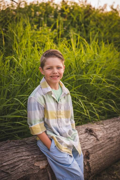 Boy sitting on a fallen tree by Seattle family photographer issaquah family photographer Bellevue family photographer
