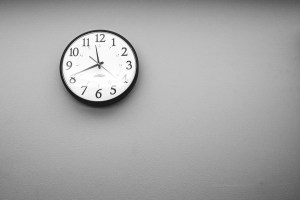 A clock on the wall of a labor and delivery room, stating the time of 11:42 PM.