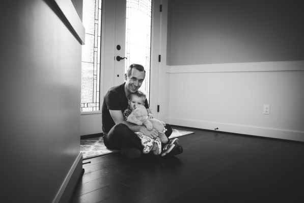 A father and his young toddler son sitting together in front of a door in a hallway during a family photography session in Seattle taken by a Seattle Family Photographer