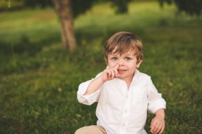 Boy picking his nose while sitting for a photo by a Seattle family photographer