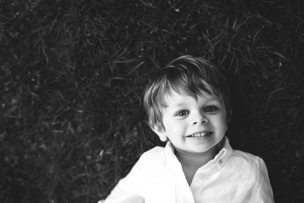 Young boy laying on the grass and smiling at the Seattle family photographer and Issaquah family photographer