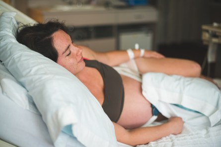 Pregnant woman laying on hospital bed by Seattle birth photographer