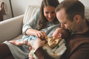 Family gazing at a newborn baby