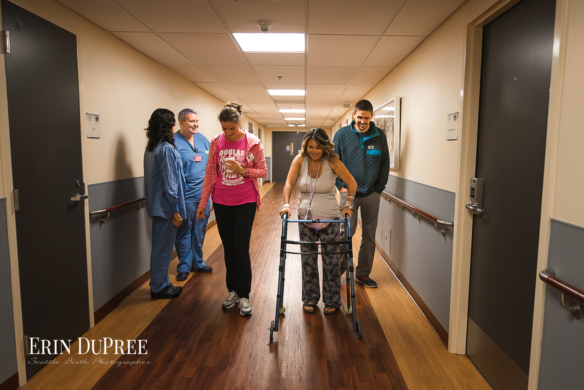 Pregnant Woman walking down a hall with nurses and doula Seattle Birth Photographer