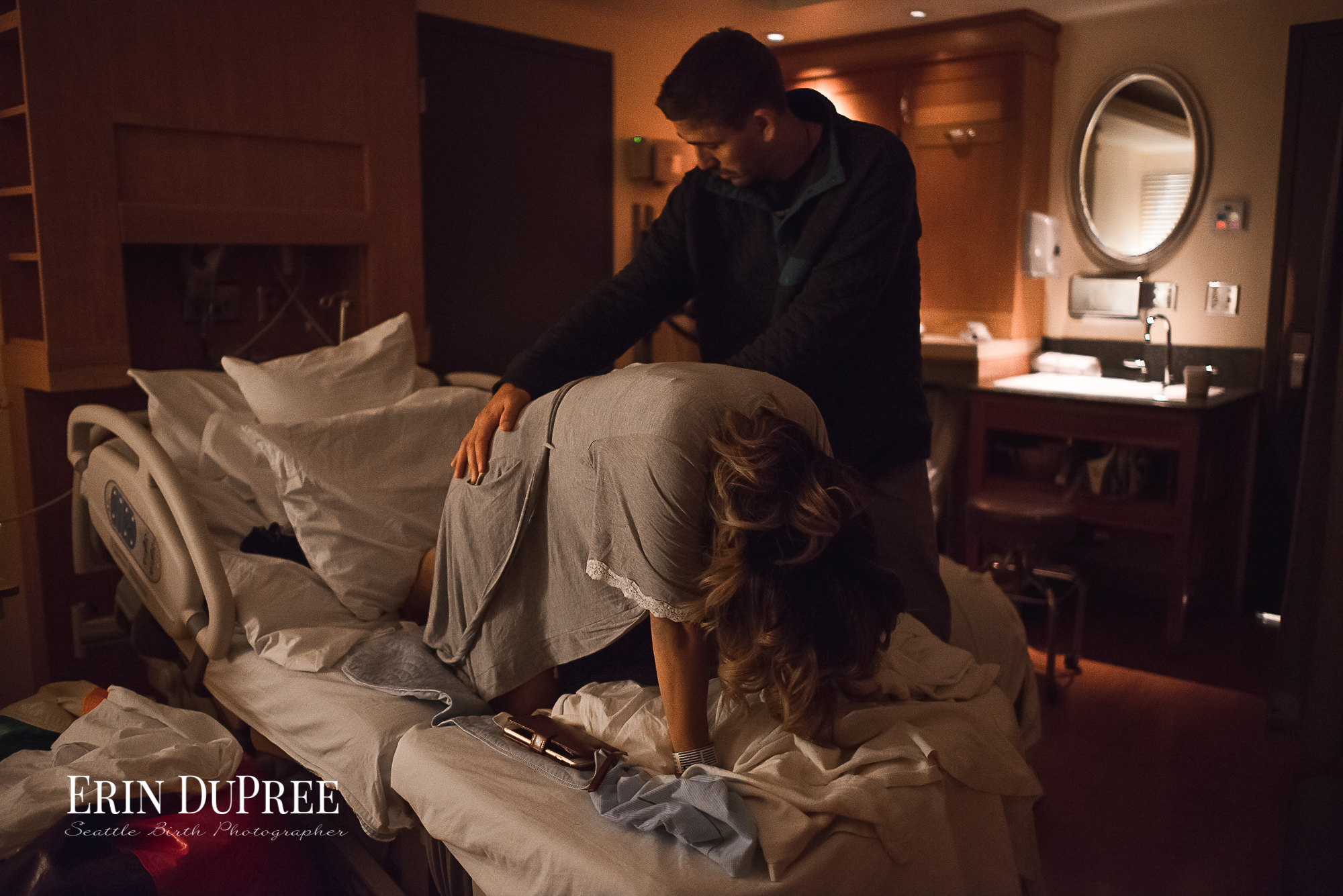 Woman in labor on all fours in a dark birthing room by Seattle Birth Photographer