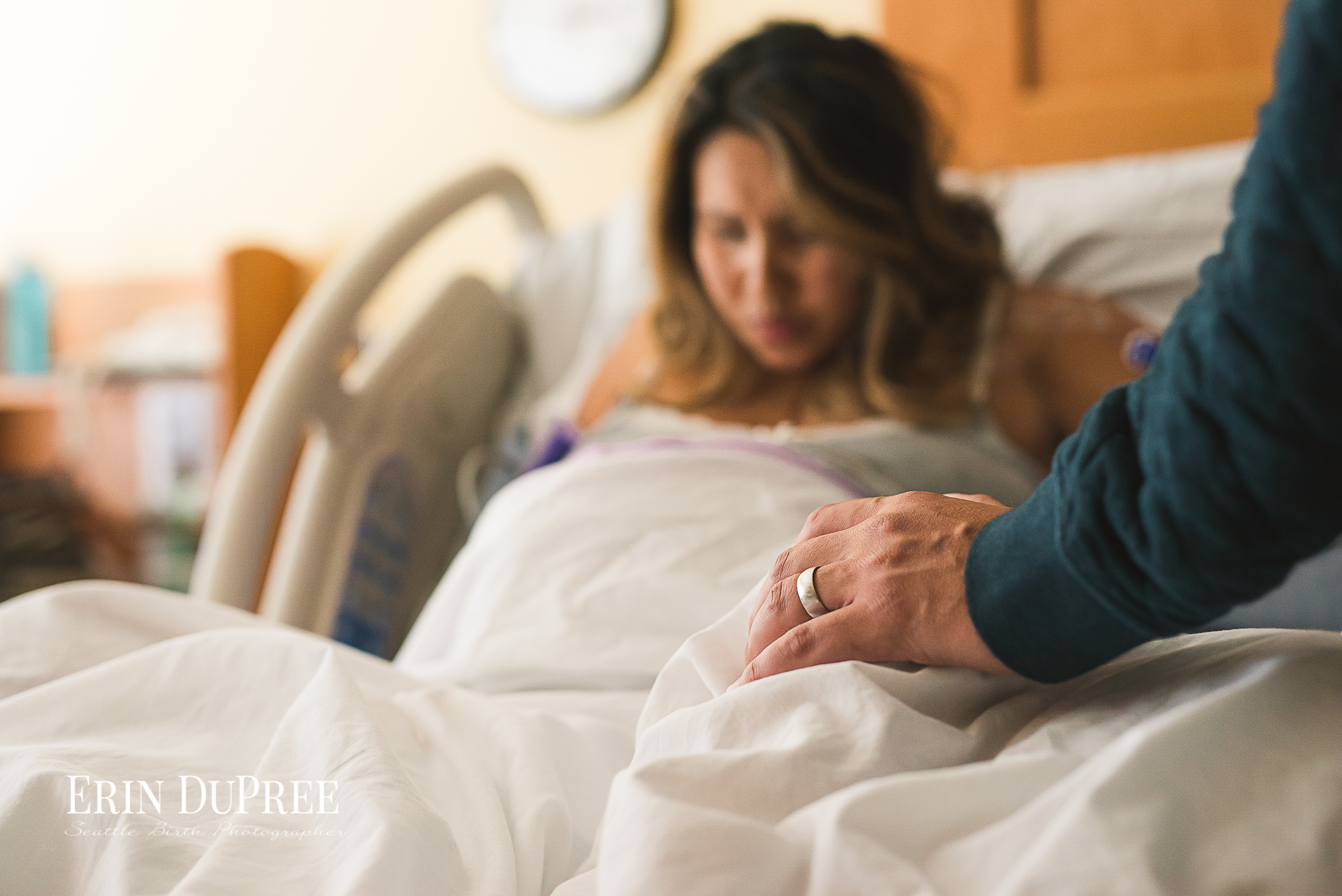 Man rests his hand on laboring wife's knee by Seattle Birth Photographer
