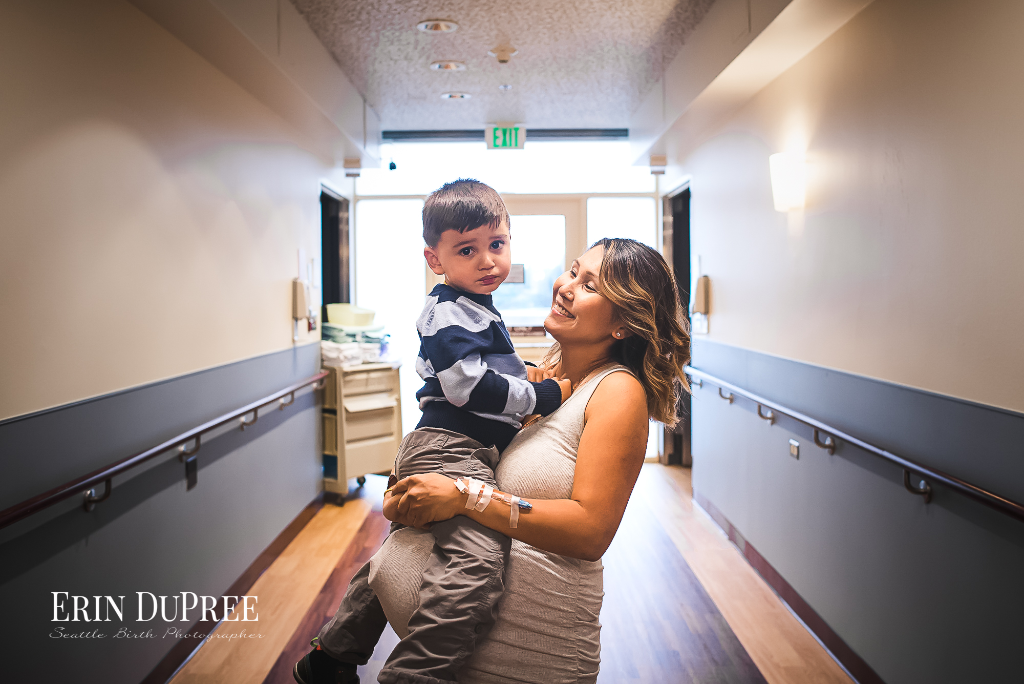 Pregnant mom holding son in hallway by Seattle Birth Photographer