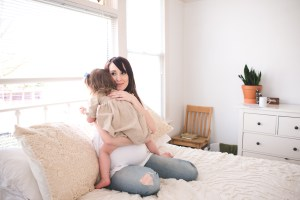 Mother holding her young child in a white room