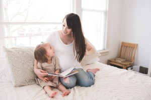 Mother looking at her young daughter holding a book