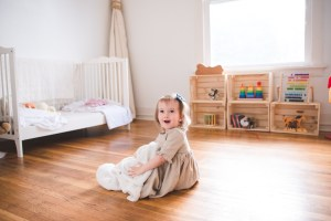 Toddler girl sitting on a bedroom floor by Seattle Family Photographer