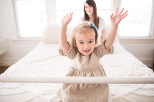 Toddler girl holding her arms up in the air by Seattle Family Photographer