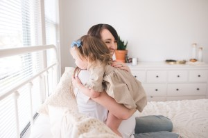 Mother holding her child in a white room
