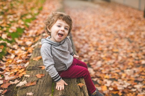 Young boy smiling at camera with autumn leaves taken by Bellevue Family Photographer Erin DuPree