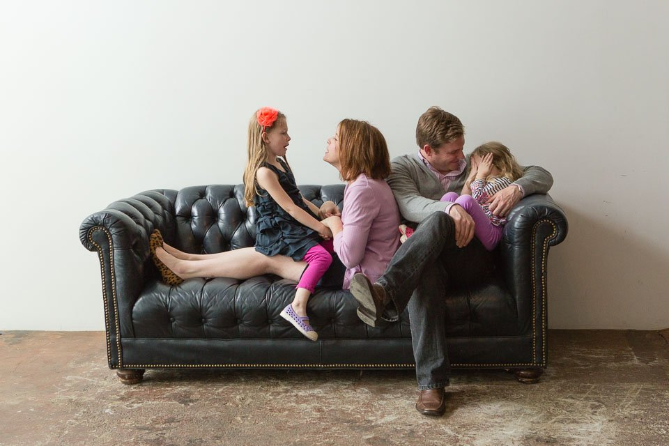 Family of 4 playing on a leather couch