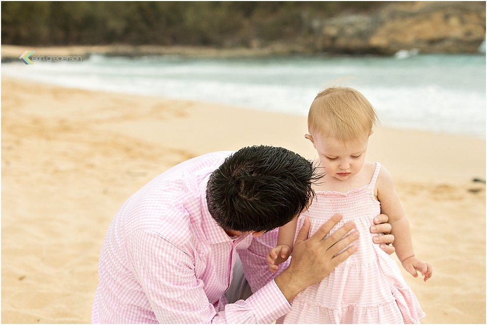 family photographer in kauai-father peering into daughter's face on beach by erin gregerson photography