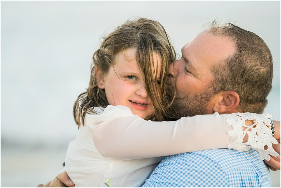 Father kissing daughter's cheek she looks ar camera with wind blown hair Kauai family photography