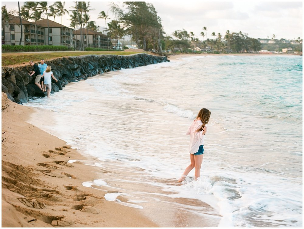 girl in Kauai beach surf at sunset by Kauai beach photographer Erin Gregerson
