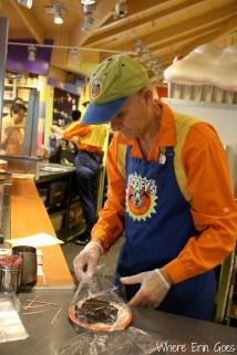 A cast member makes a custom treat at Goofy's Candy Co.