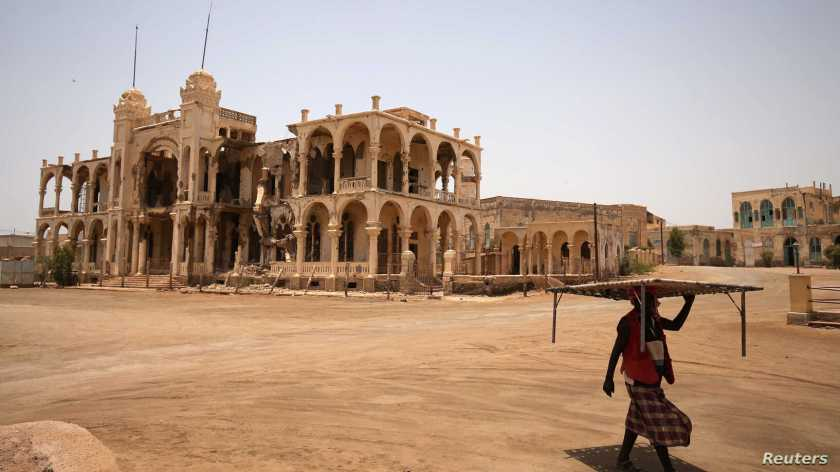 A man carries a table as he walks past the ruins of a building in the port city of Massawa