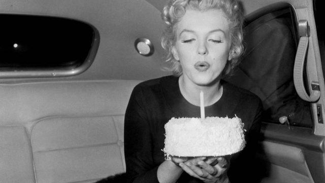 Marilyn Monroe soplando la vela de un pastel de cumpleaños