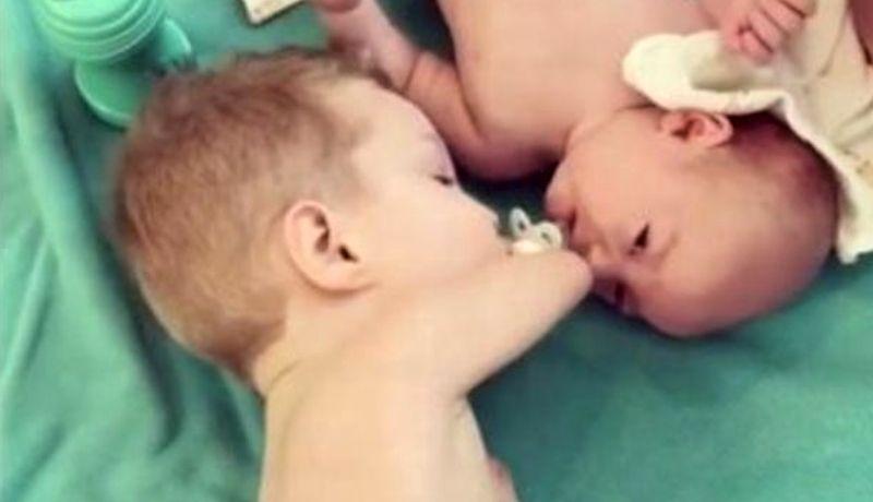 Niño sin brazos le da chupón a bebé