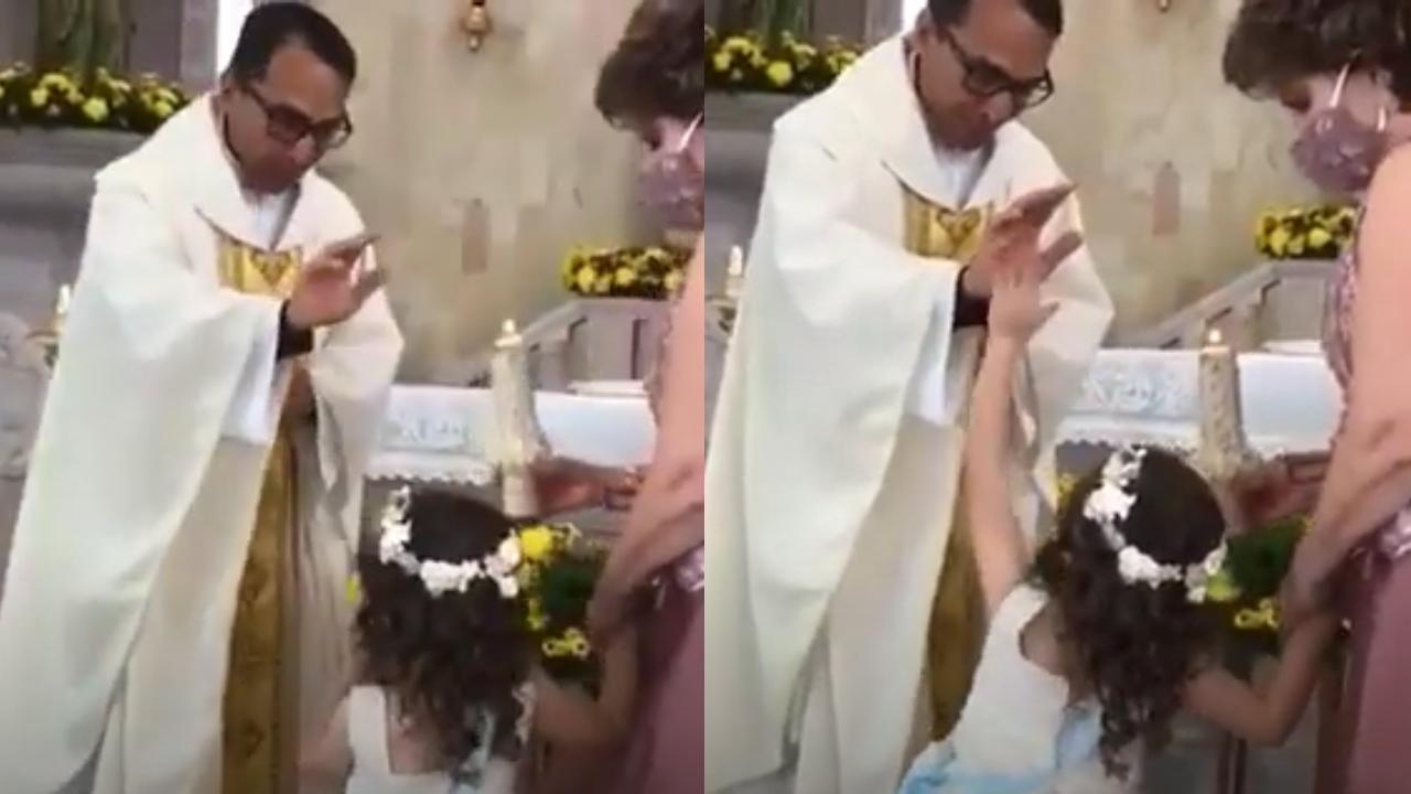 Niña choca la mano con sacerdote
