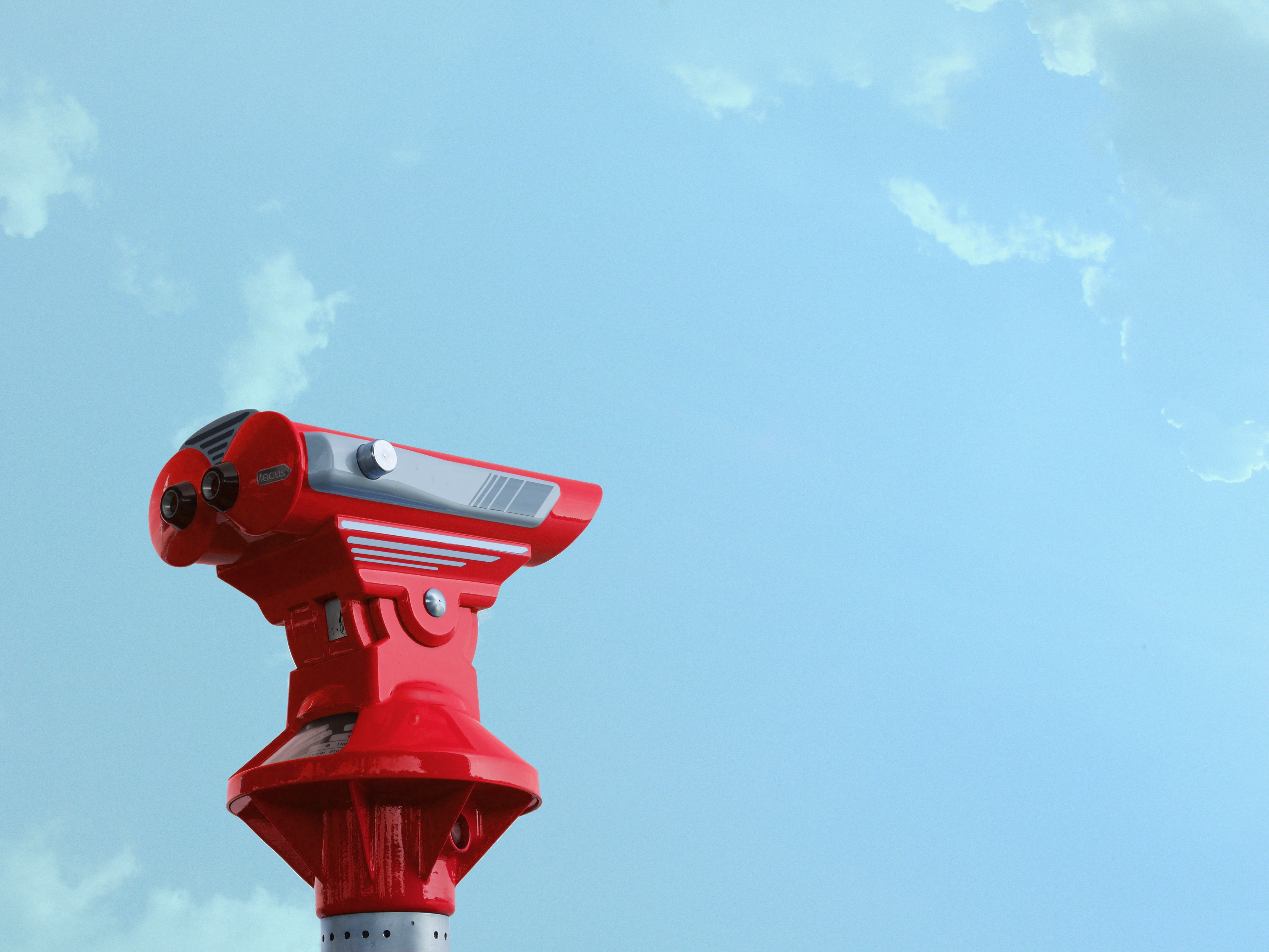 red binoculars with sky background