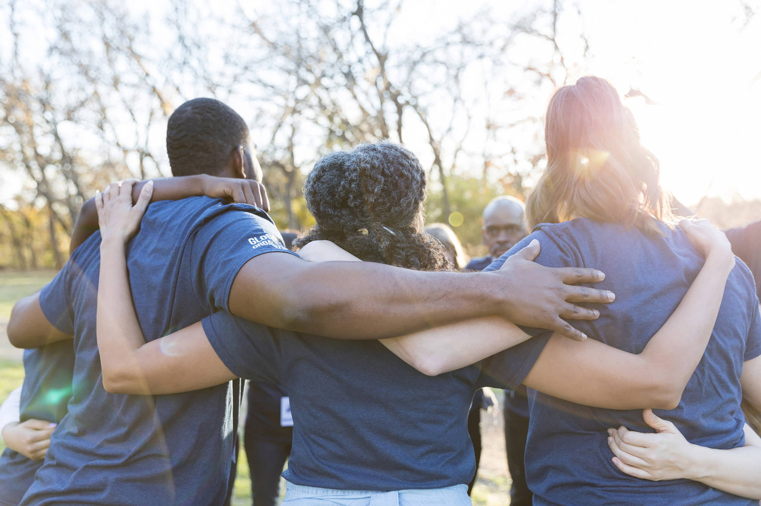 rear view of a group of people with arms around eachother