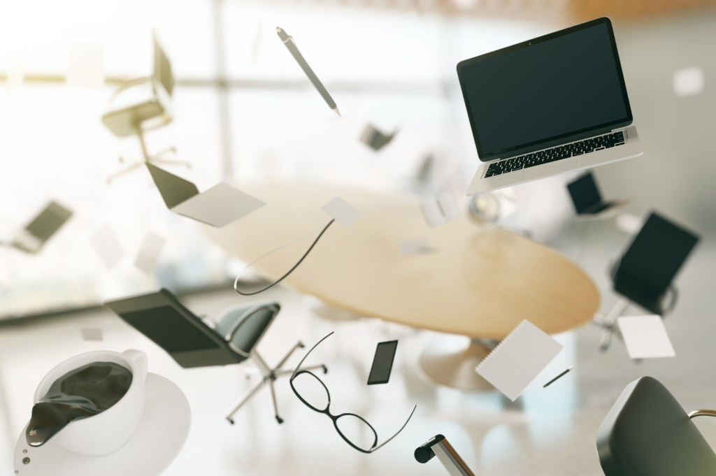many desk objects flying in air such as a computer, paper and glasses