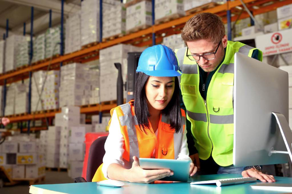 one female and one male building material professionals wearing neon vests and look at tablet