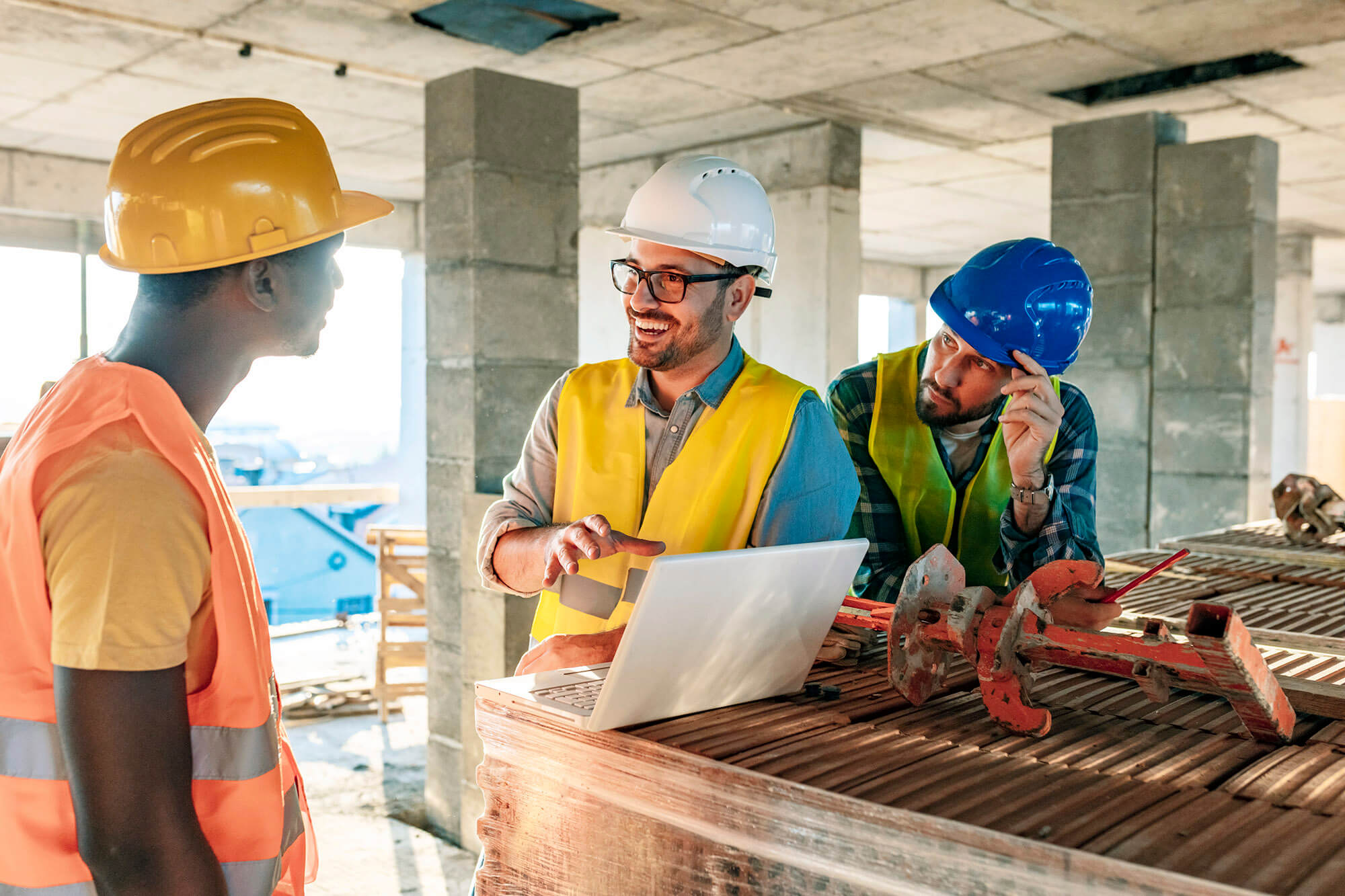 three med with hard hats and neon vests smile and discuss in front of a laptop on a worksite