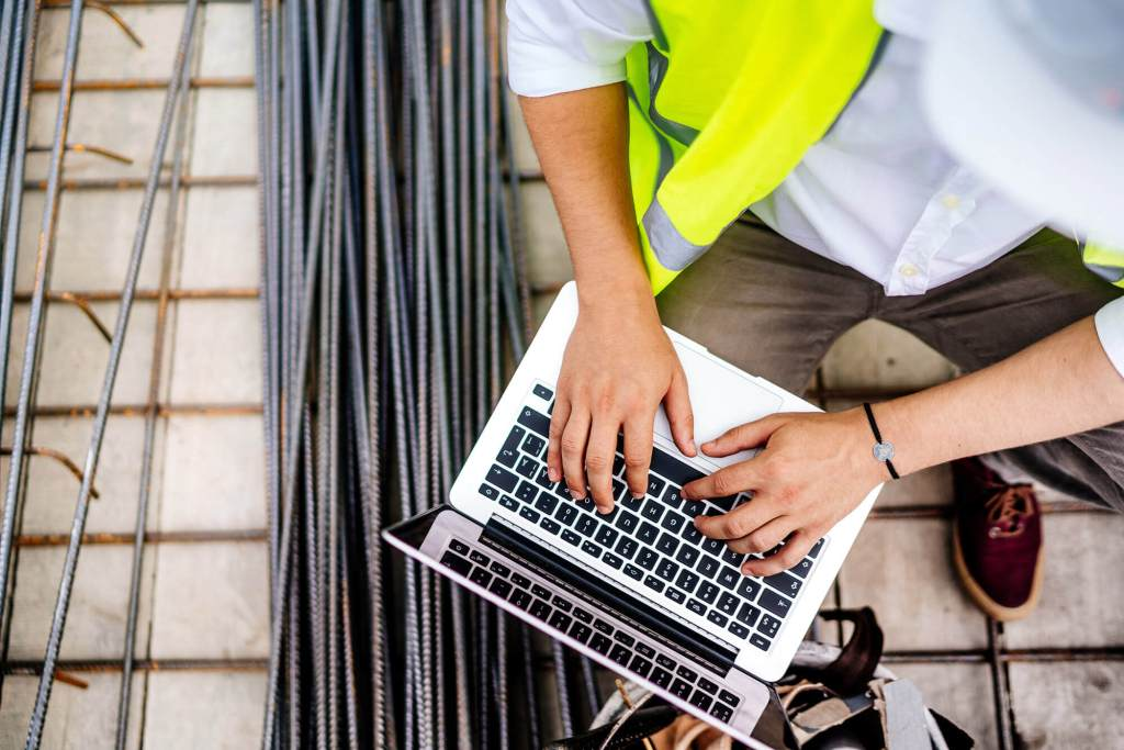 close up of construction worker typing on laptop