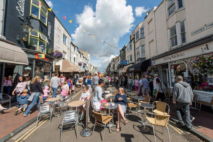 People eat at outdoor tables in North Laine, Brighton