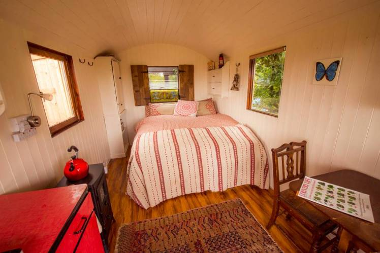 Bed pulled out inside glamping hut at Iford