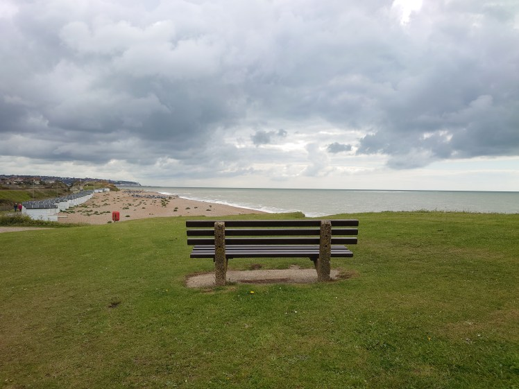 A lone bench overlooks the beach on walk from Hastings Bexhill-on-Sea