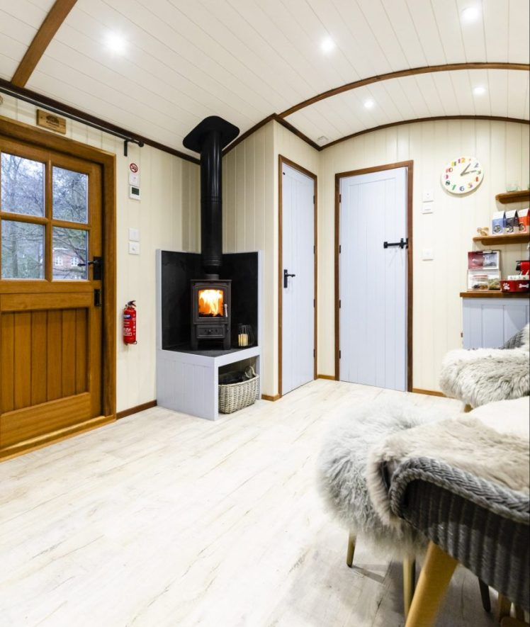 Inside a shepherds hut at The Merry Harriers complete with wood burner and fluffy blankets over seats