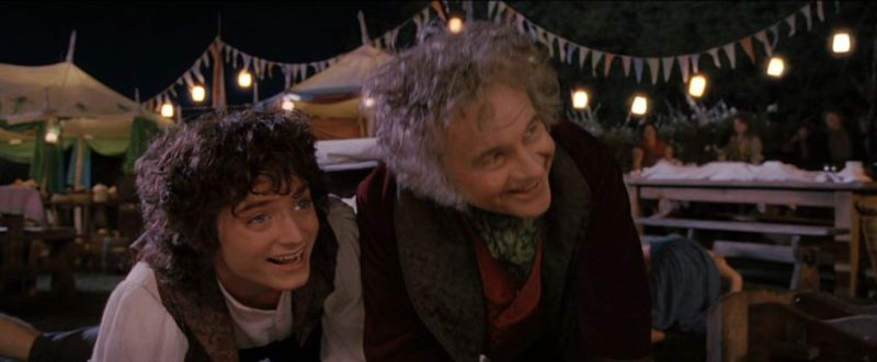 Frodo et Biblo accroupis et souriants lors d'une fête