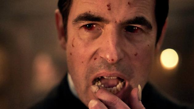 Dracula a le visage constellé de sang et se léche les doigts